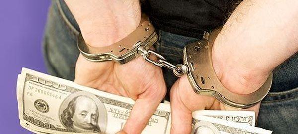 Арестованный аферист с деньгами в наручниках